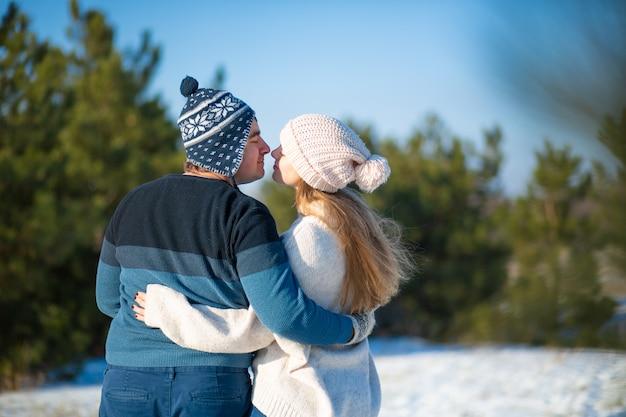 Marche D'hiver à Travers Les Bois. Vue Arrière Un Gars Avec Une Fille Dans Une étreinte Marcher Dans La Forêt Photo Premium