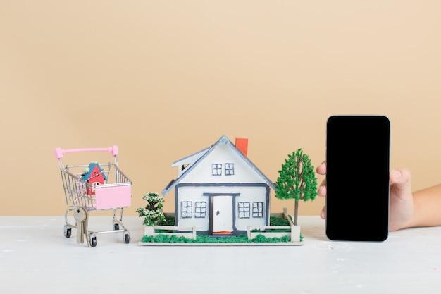Marché immobilier avec maison, caddie et téléphone Photo gratuit