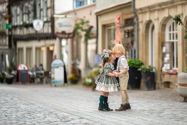 Marcher des enfants dans la rue. la relation d'une fille et d'un garçon. photos dans un style rétro. pavés dans le centre-ville. été.allemagne Photo Premium