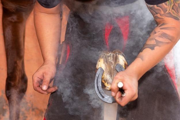 Maréchal-ferrant plaçant la griffe sur le sabot du cheval. Photo Premium