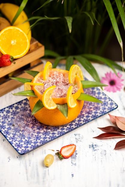 Margarita cocktail d'été rafraîchissante avec glace concassée et agrumes à l'intérieur de l'orange dans une assiette décorative authentique Photo gratuit