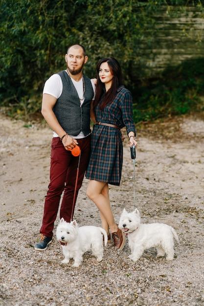 Mari Avec Une Belle Femme Promener Leurs Chiens Blancs Dans Le Parc Photo Premium