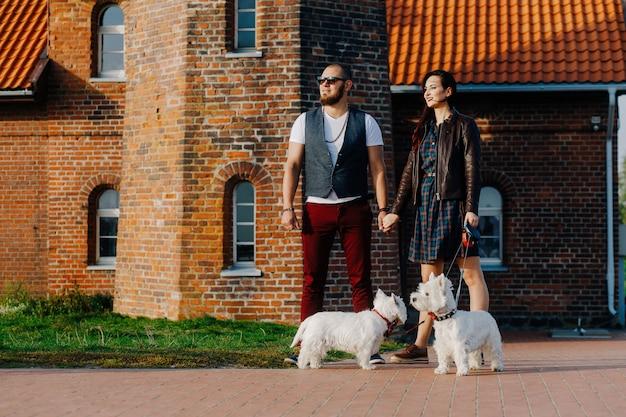 Mari Avec Une Belle Femme Promener Leurs Chiens Blancs Dans La Rue Photo Premium