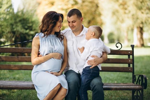Mari avec femme enceinte et leur fils dans le parc Photo gratuit