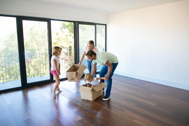 Mari, Femme Et Leurs Filles Jouant Avec Des Boîtes Et Emménageant Dans Une Nouvelle Maison Photo gratuit
