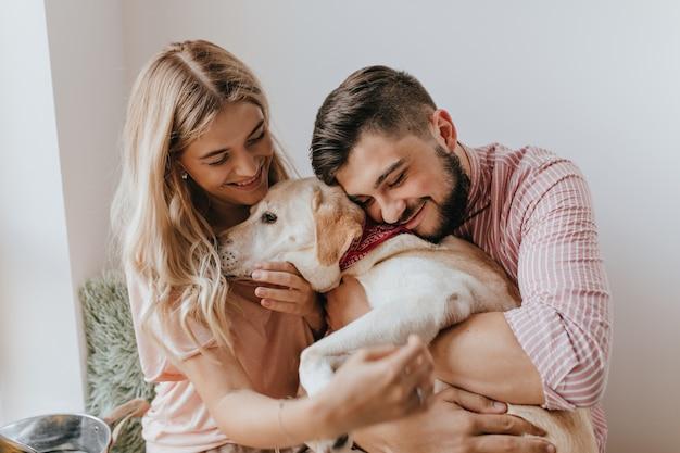 Un Mari Et Une Femme Positifs Jouent Avec Un Chien. L'homme En Chemise Rayée Embrasse Le Labrador Avec Tendresse. Photo gratuit
