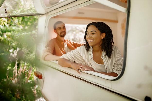 Mari Et Femme Regarde Par La Fenêtre Du Camping-car, Campant Dans Une Remorque. Homme Et Femme Voyagent En Van, Vacances Romantiques En Camping-car, Loisirs Campeurs En Camping-car Photo Premium