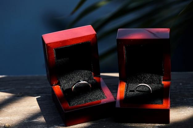Mariage bagues en diamant dans une boîte brillante rouge sur le vieux fond en bois avec tache Photo Premium