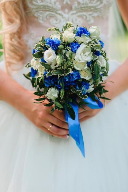 Mariage beau bouquet de roses blanches et de fleurs bleues dans les mains de la mariée avec un anneau Photo Premium