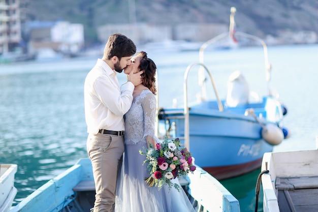 Mariage sur la jetée avec des bateaux sur la mer Photo Premium