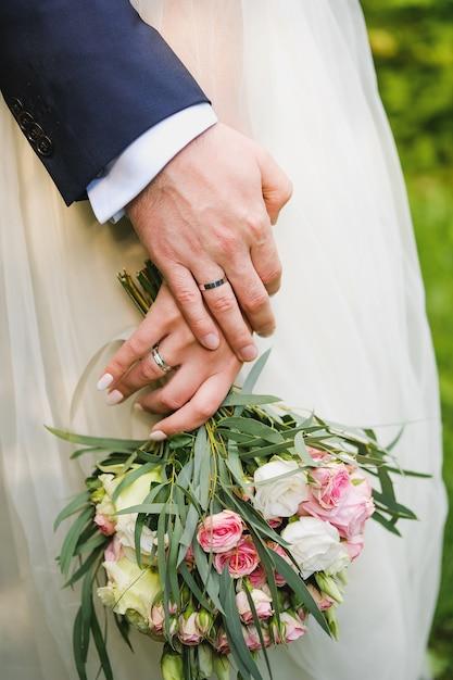 Mariage de jeunes gens, la mariée tenant un bouquet. Photo Premium