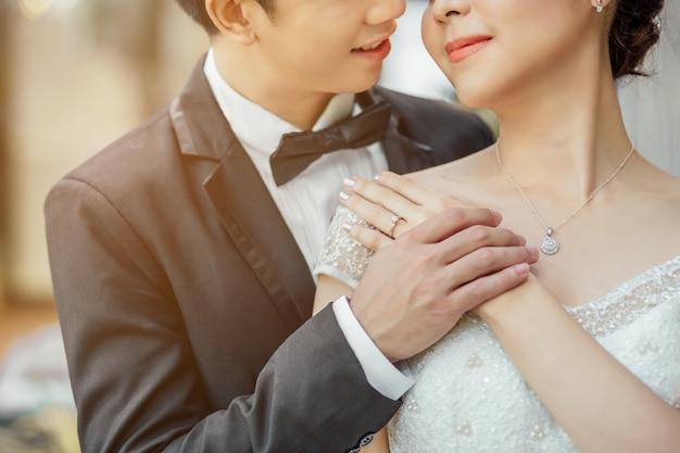 Le marié asiatique et la mariée asiatique sont très proches l'un de l'autre et sont sur le point de s'embrasser avec un visage souriant et heureux. ils se tiennent la main. Photo Premium