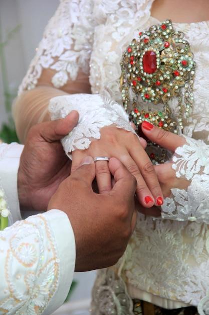 Le marié attache la bague de mariage à l'annulaire de la mariée Photo Premium