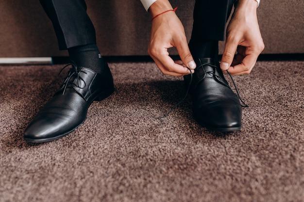 Le Marié Attache Des Lacets Sur Ses Chaussures Assis Sur Un Canapé Photo gratuit