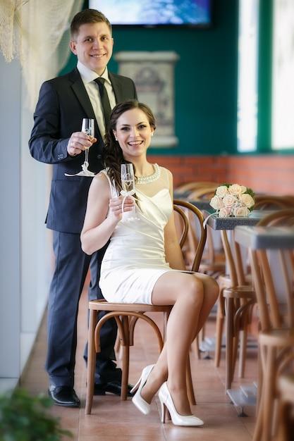 Marié avec une coupe de champagne et la mariée avec un bouquet de roses au café Photo Premium