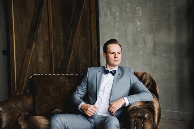 Le marié dans un costume gris, une chemise blanche et un nœud papillon est assis sur un canapé en cuir marron. Photo Premium