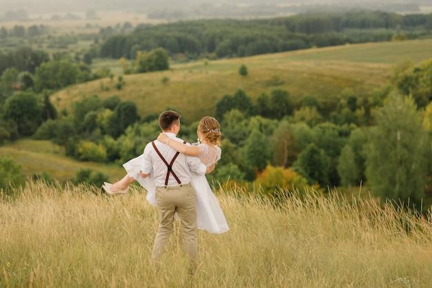Le Marié Encercle Dans Ses Bras Une Belle Mariée, Le Marié Heureux Tient Dans Ses Bras Sa Belle Mariée, Contre Un Beau Paysage. Jour De Mariage. Photo Premium