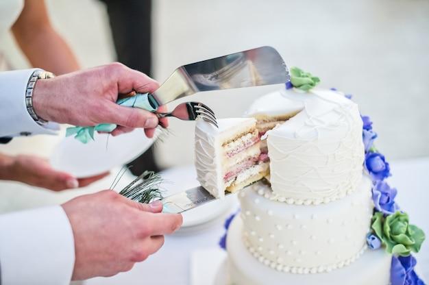 Le marié et la mariée coupent un gâteau de mariage blanc décoré de fleurs bleues Photo Premium