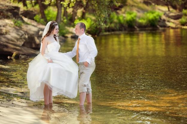 Le marié et la mariée sur une plage le jour de leur mariage Photo Premium