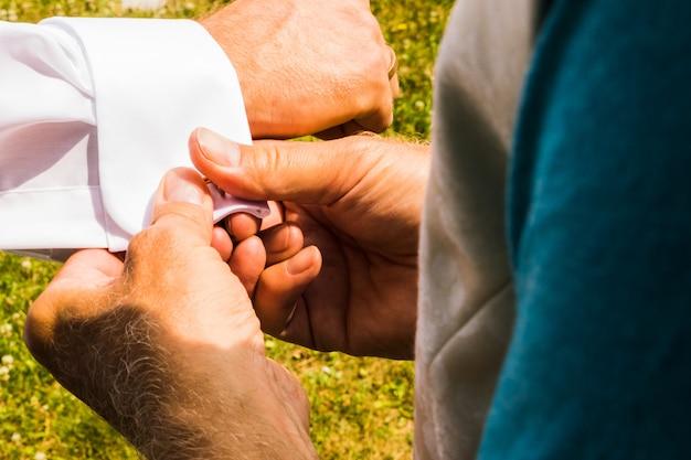 Un marié met des boutons de manchette alors qu'il s'habille le jour de son mariage. costume du marié Photo Premium