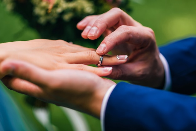 Le marié met la mariée une alliance en or blanc à son doigt Photo Premium