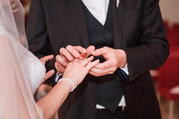 Marié mettre une bague sur le doigt de la mariée. Photo Premium
