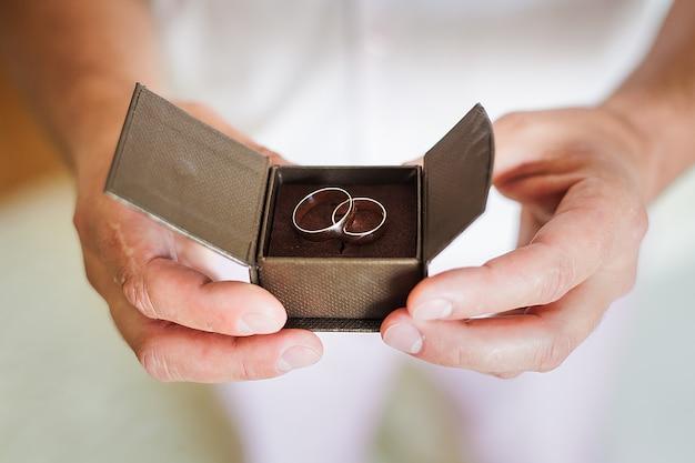 Marié tenant belle boîte avec des alliances Photo Premium