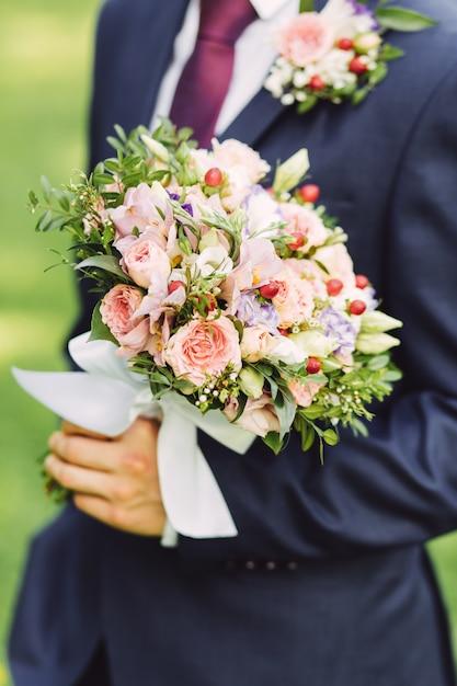 Marié tenant un bouquet de roses, gros plan Photo Premium