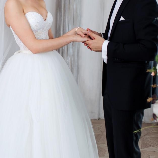 Le marié tient la main de la mariée, voeux de mariage. Photo Premium