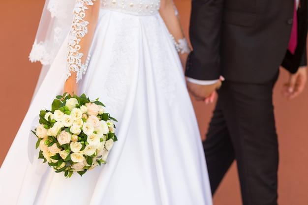 Le marié tient la main de la mariée Photo Premium