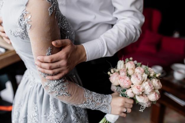 Le marié tient sa main bien-aimée Photo gratuit