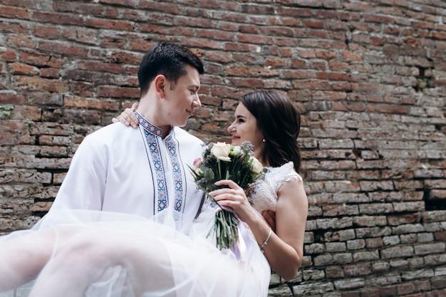Le marié tourbillonne mariée sur ses bras debout devant un mur de briques Photo gratuit
