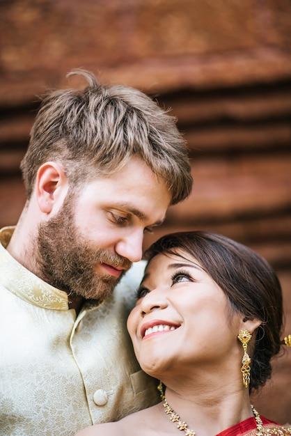 Mariée asiatique et marié caucasien ont du temps romantique avec la robe de la thaïlande Photo gratuit