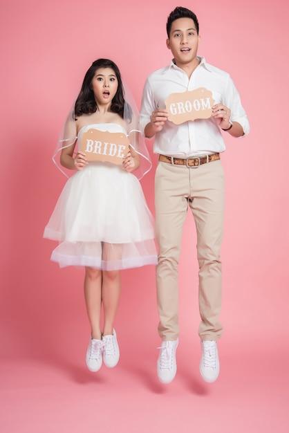Mariée asiatique marié sautant Photo Premium