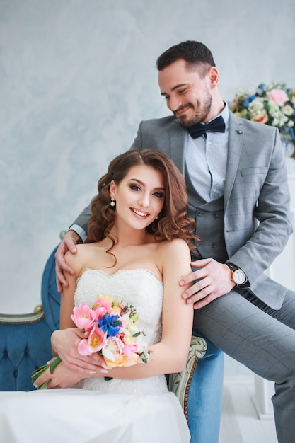 Mariée En Belle Robe Et Le Marié En Costume Gris Assis Sur Le Canapé à L'intérieur. Style De Mariage à La Mode Photo Premium