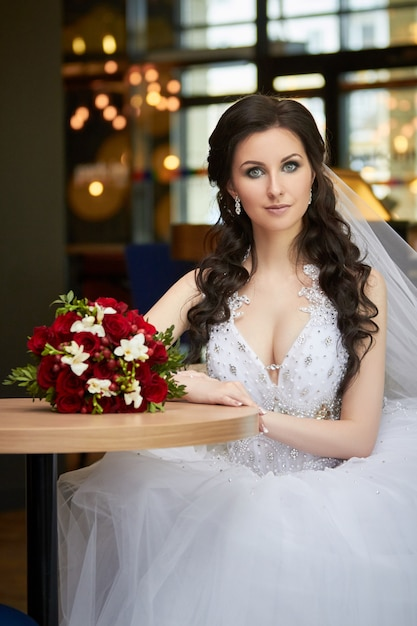 Mariée avec un bouquet de fleurs assis à table Photo Premium