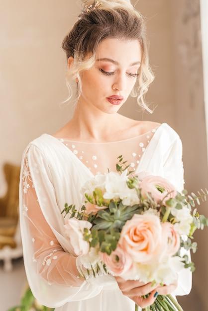 Mariée avec bouquet de fleurs Photo gratuit
