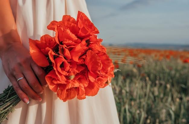 Mariée Dans Une Robe Blanche Tenant Un Bouquet De Fleurs De Pavot, L'heure Du Coucher Du Soleil Chaud Sur Le Champ De Pavot Rouge. Copiez L'espace. Photo Premium