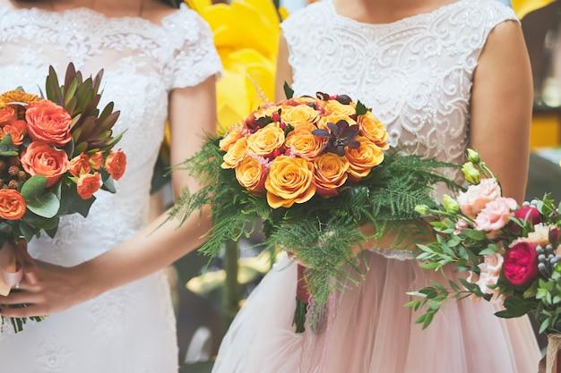 La mariée dans une robe blanche tient dans ses mains un beau bouquet de mariage de roses orange Photo Premium