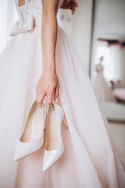La mariée dans sa robe de mariée tient ses élégantes chaussures beiges dans ses mains. Photo Premium