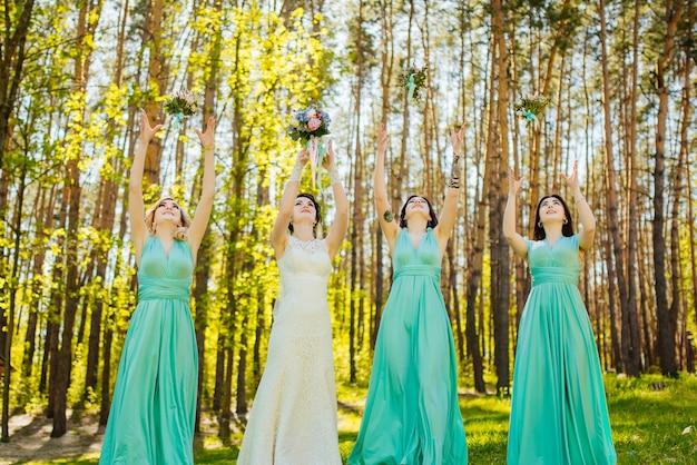 Mariée et demoiselles d'honneur jetant des bouquets de mariage. Photo gratuit