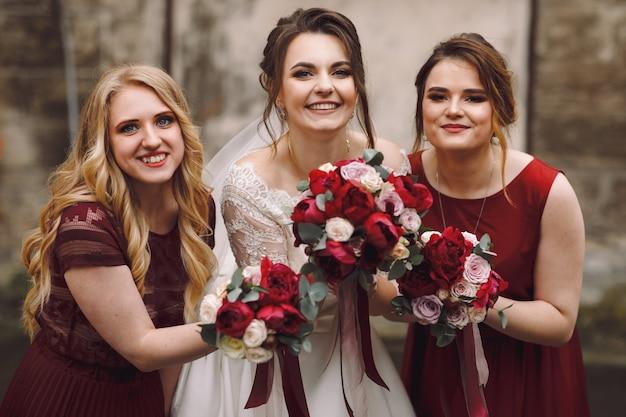 La mariée et les demoiselles d'honneur en robes rouges posent à l'extérieur sur la vieille rue humide Photo gratuit