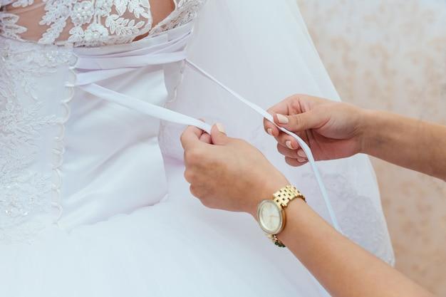 Mariée du matin. demoiselle d'honneur aider le laçage de sa robe Photo Premium