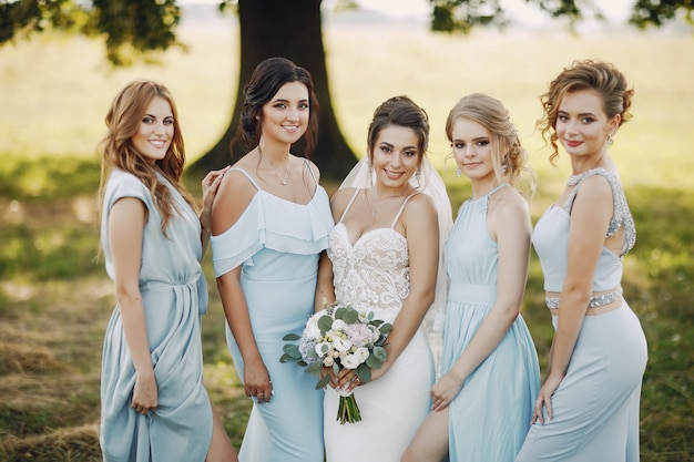 Mariée élégante et élégante avec ses quatre amis en robes bleues debout dans un parc Photo gratuit