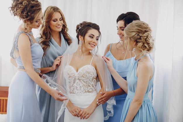 Mariée élégante et élégante avec ses quatre amis en robes bleues debout dans une pièce Photo gratuit