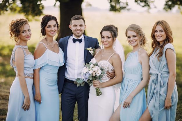 Mariée élégante et élégante avec ses quatre amis en robes bleues et son mari Photo gratuit
