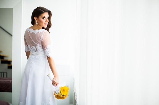 Mariée enceinte avec un bouquet de tournesols Photo Premium
