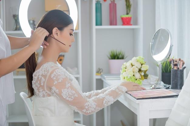 Mariée faire les cheveux avec la robe Photo gratuit