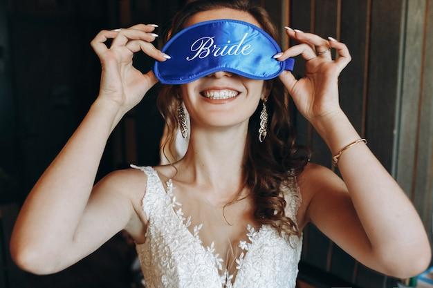 7a3f0b2fb71f0 Mariée gaie tient le masque de sommeil bleu devant ses yeux Photo Premium