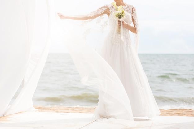 Mariée heureuse avec boquet sur la plage. Photo Premium